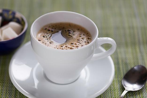 Tazza di caffè bianco, cucchiaino e zucchero su un tavolo Foto Premium