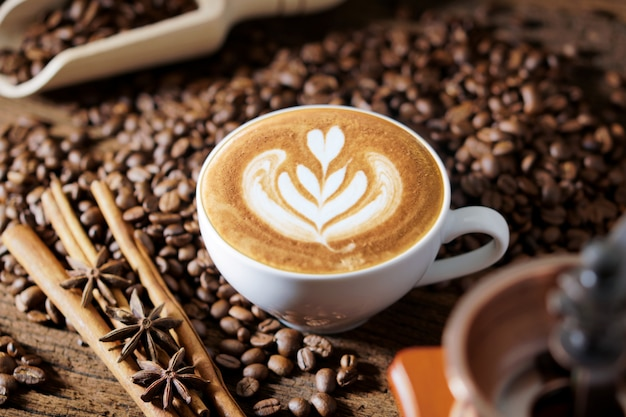 Tazza di caffè bianco e chicchi di caffè tostato in giro Foto Premium