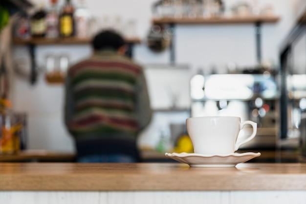Tazza di caffè bianco e piattino sul bancone del caffè Foto Gratuite
