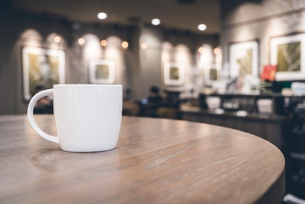 Tazza di caffè bianco in caffetteria Foto Gratuite