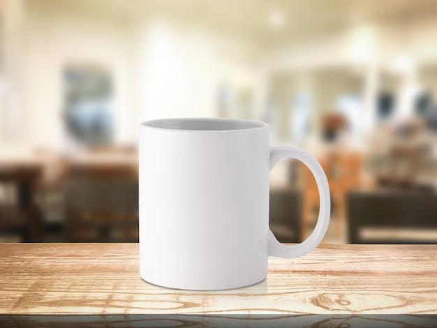 Tazza di caffè bianco o tazza della bevanda sul ristorante della sfuocatura Foto Premium