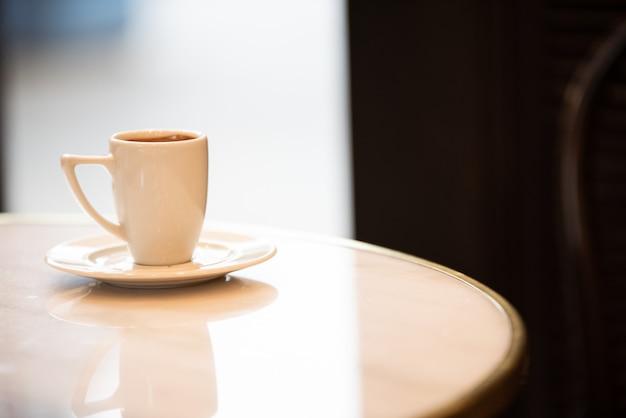 Tazza di caffè bianco su un tavolo di marmo all'interno di un caffè. Foto Premium