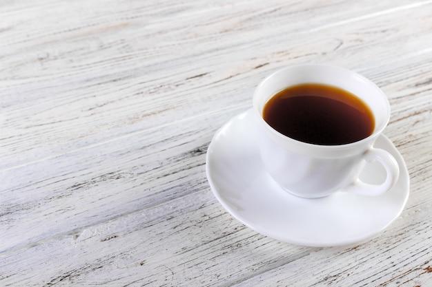 Tazza di caffè bianco su vecchio di legno Foto Premium
