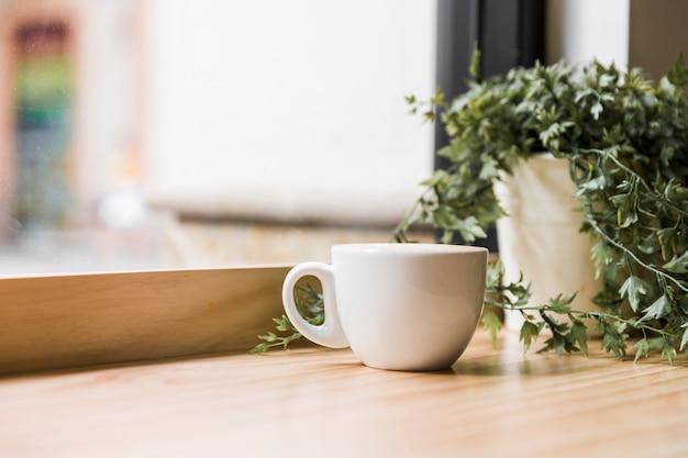 Tazza di caffè bianco sul ripiano del tavolo in legno Foto Gratuite