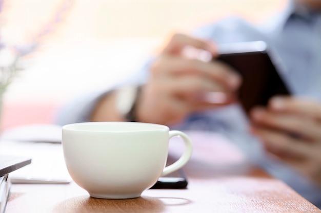 Tazza di caffè bianco sulla tavola di legno in caffè con illuminazione e l'uomo vago di immagine che usando il fondo dello smartphone. Foto Premium