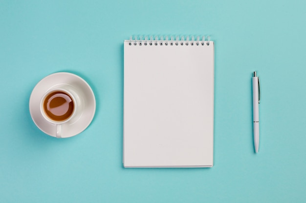 Tazza di caffè, blocco note a spirale in bianco e penna sulla scrivania blu Foto Gratuite