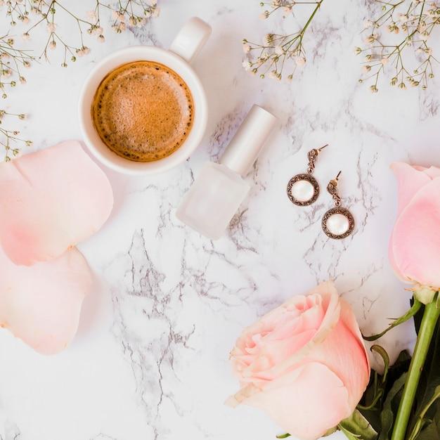 Tazza di caffè; bottiglia di smalto per unghie; rose; orecchini e fiori baby's-breath su sfondo con texture Foto Gratuite