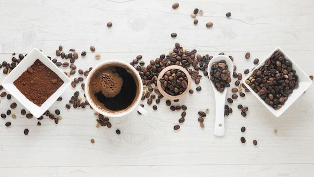 Tazza di caffè; caffè in polvere e chicchi di caffè disposti in fila sulla scrivania Foto Gratuite