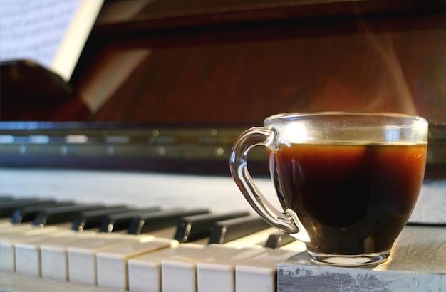Tazza di caffè caldo con fumo con la tastiera del piano sfocato in background Foto Premium