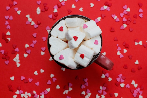 Tazza di caffè caldo con marshmallow a forma di cuore e confetti su rosso Foto Gratuite