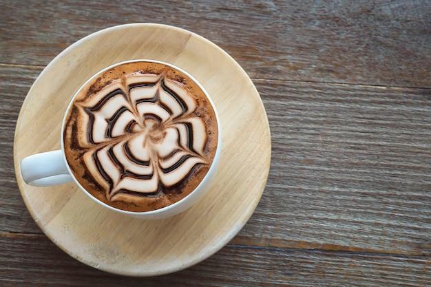 Tazza di caffè caldo d'annata con la bella decorazione di arte del latte sulla vecchia tavola di legno di struttura Foto Gratuite