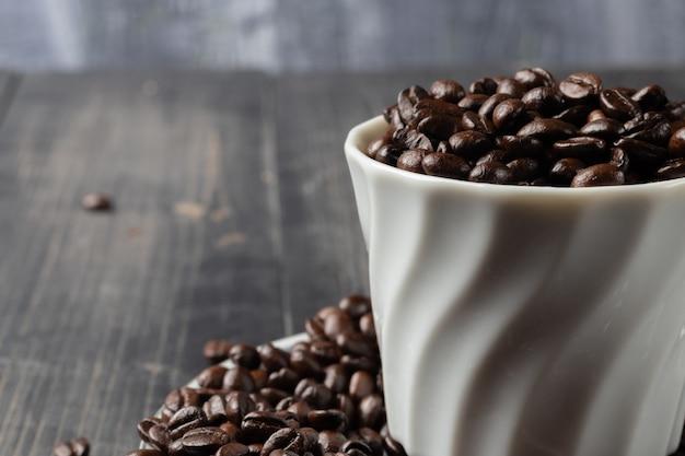 Tazza di caffè caldo e chicchi di caffè tostato Foto Premium