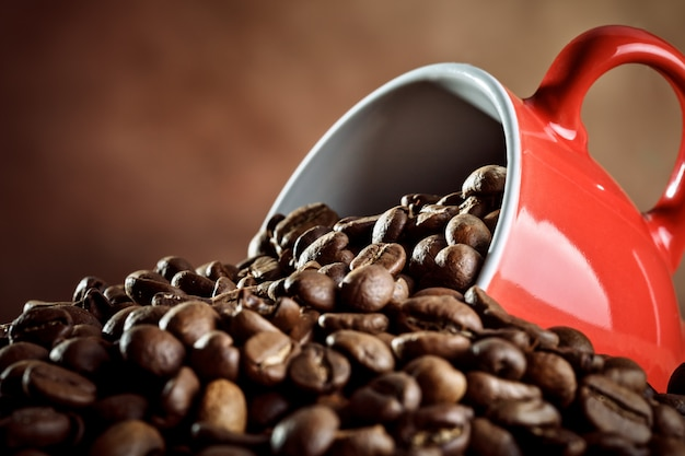 Tazza di caffè ceramica rossa che si trova in chicchi di caffè caldi. Foto Premium