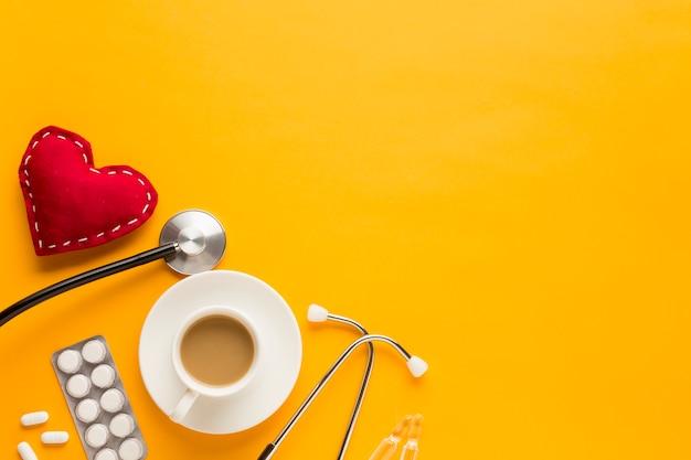 Tazza di caffè; compresse confezionate in blister; stetoscopio e cucito a forma di cuore su sfondo giallo Foto Gratuite