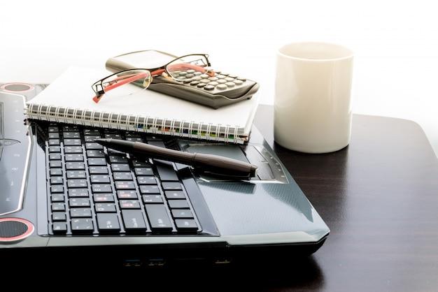 Tazza di caffè, computer portatile, penna, calcolatrice, blocco note e bicchieri sul tavolo di legno Foto Premium