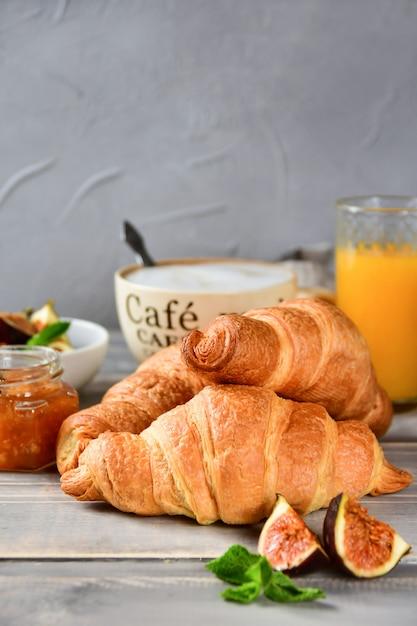Tazza di caffè con latte e cornetti su un tavolo di legno. Foto Premium