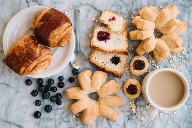 Tazza di caffè con panetteria diversa sul tavolo di marmo Foto Gratuite