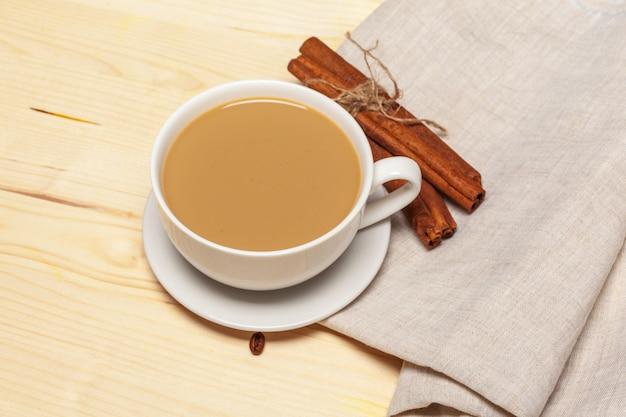 Tazza di caffè con piattino su una vista dall'alto di sfondo in legno Foto Premium