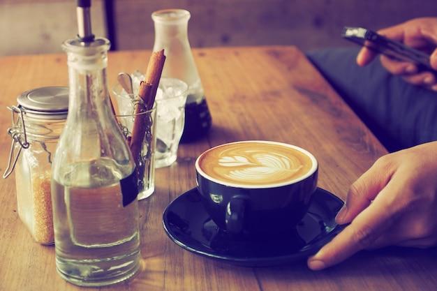 Tazza di caffè con una bottiglia d'acqua e un bicchiere con bastoncini di cannella su un tavolo di legno Foto Gratuite