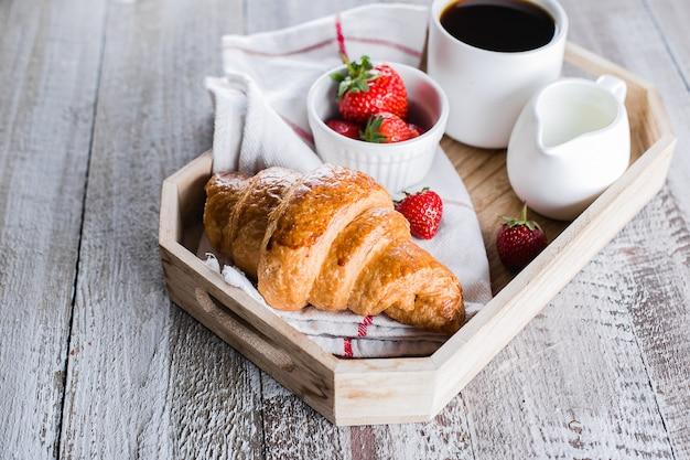 Tazza di caffè, cornetti appena sfornati e fragole fresche sul vassoio di legno. Foto Premium