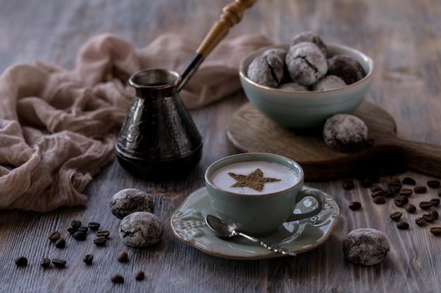 Tazza di caffè crema con biscotti al cioccolato, marshmallow e candele accese. Foto Premium