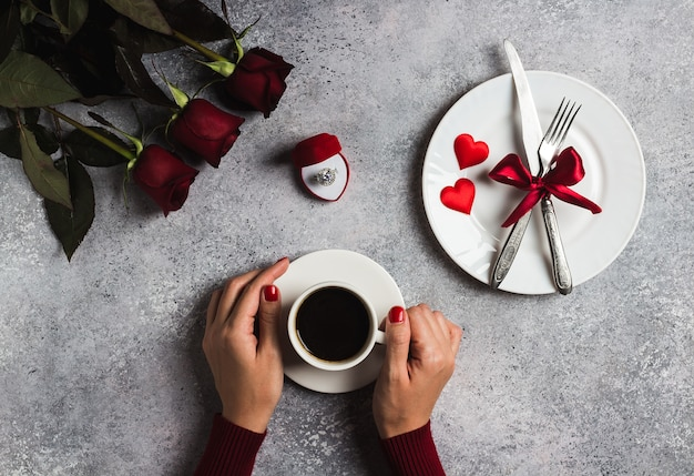Tazza di caffè della mano della donna della regolazione della tavola romantica di giorno di biglietti di s. valentino della tenuta Foto Gratuite