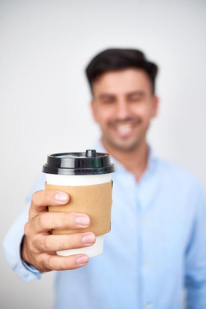 Tazza di caffè di carta della tenuta dell'uomo Foto Gratuite