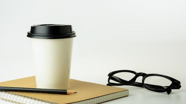 Tazza di caffè di carta e un taccuino sul fondo bianco dello scrittorio con lo spazio della copia. - forniture per ufficio o concetto di educazione. Foto Premium