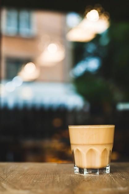 Tazza di caffè di vetro sullo scrittorio di legno con il contesto di caf� di defocus Foto Gratuite