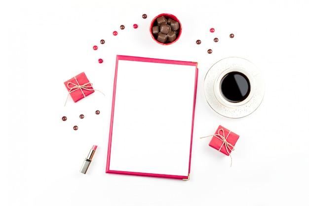 Tazza di caffè, dolci al cioccolato, confezione regalo e pezzo di carta bianco disteso. sfondo femminile. Foto Premium