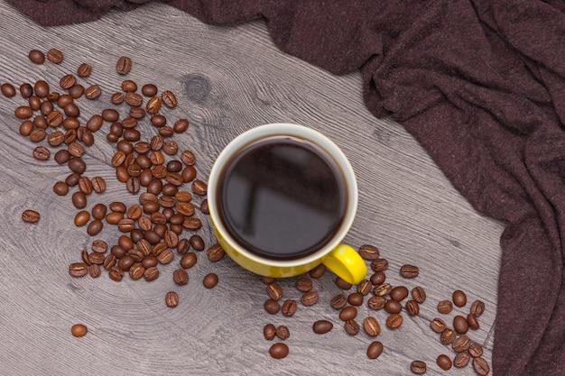 Tazza di caffè e chicchi di caffè gialli su legno Foto Premium
