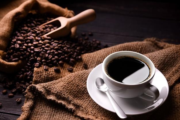Tazza di caffè e chicchi di caffè nel sacco di iuta su fondo in legno vecchio Foto Premium