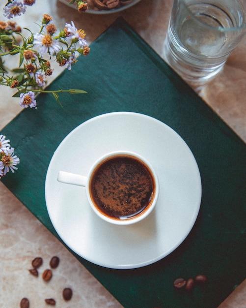 Tazza di caffè e chicchi di caffè sul tavolo Foto Gratuite