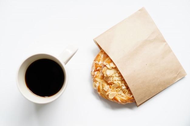 Tazza di caffè e cornetto con pianificazione del viaggio di vacanza e pronto per partire Foto Premium
