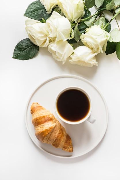 Tazza di caffè e croissant appena sfornati. vista dall'alto. copia spazio Foto Premium