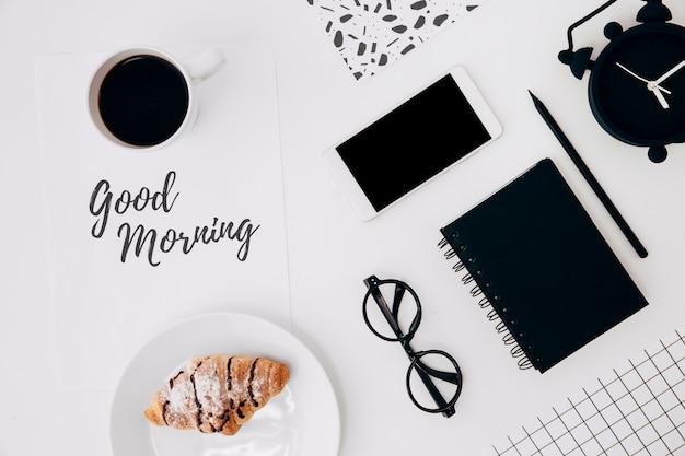 Tazza di caffè e croissant con messaggio di buongiorno su carta e ufficio stazionari sulla scrivania bianca Foto Gratuite