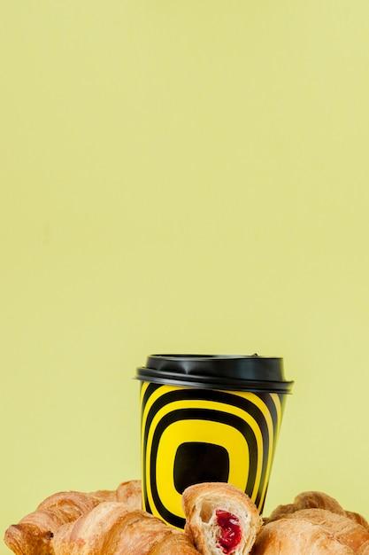 Tazza di caffè e croissant di carta su un giallo Foto Premium