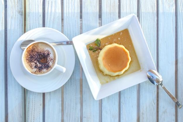 Tazza di caffè e dessert di panna cotta su una tavola di legno. Foto Premium