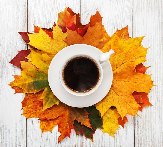 Tazza di caffè e foglie d'autunno Foto Premium