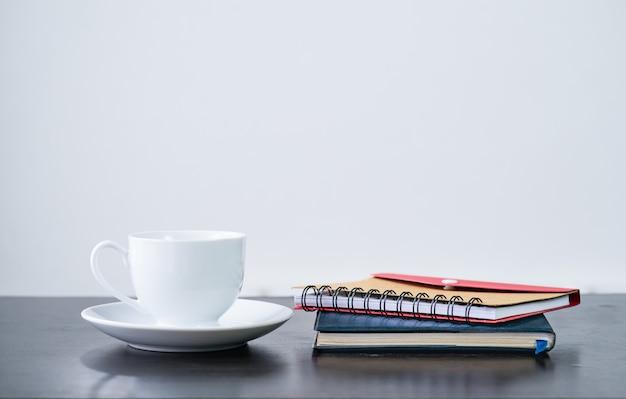 Tazza di caffè e notebook sulla scrivania Foto Premium
