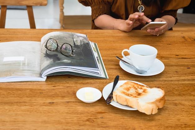Tazza di caffè e occhiali da vista con fetta di pane tostato e donna che per mezzo del telefono cellulare. Foto Premium