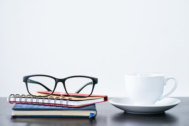 Tazza di caffè e occhiali sulla scrivania Foto Premium