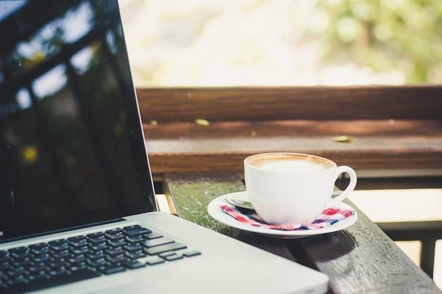 Tazza di caffè e portatile sul tavolo in caffetteria Foto Premium