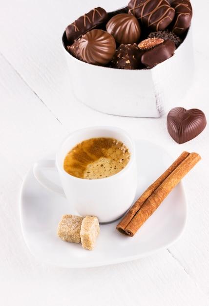 Tazza di caffè e scatola di cioccolatini su un fondo di legno bianco Foto Premium