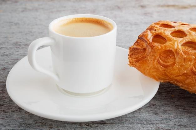Tazza di caffè espresso appena preparato e un croissant su una schiena in legno Foto Premium