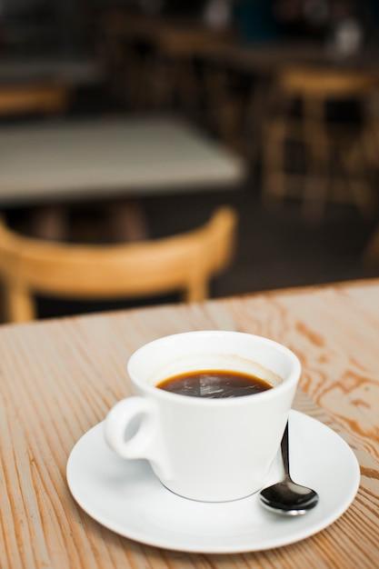 Tazza di caffè espresso con cucchiaio in acciaio inox sopra la scrivania Foto Gratuite