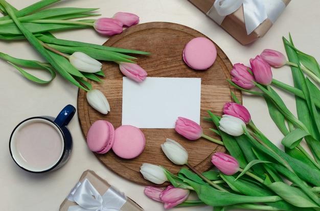 Tazza di caffè, fiori del tulipano della molla e macarons rosa sul fondo pastello di vista del piano d'appoggio Foto Premium