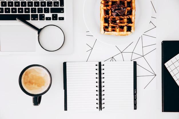 Tazza di caffè; il computer portatile; lenti d'ingrandimento; blocco note a spirale e cialde con cioccolato sul piatto contro scrivania bianca Foto Gratuite