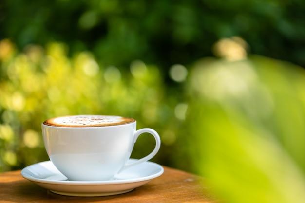 Tazza di caffè in ceramica bianca sul tavolo di legno Foto Premium