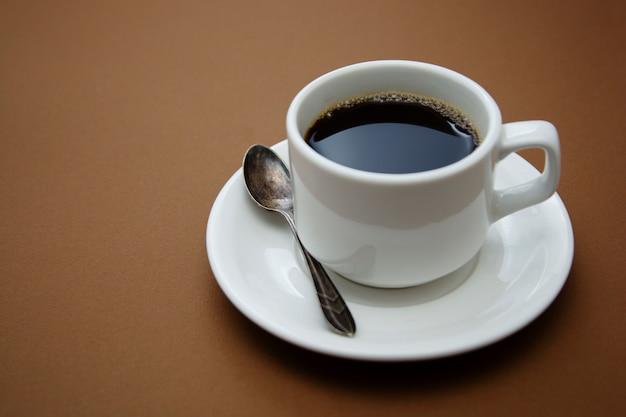 Tazza di caffè isolata sulla tavola marrone. bere caffè con spazio di copia. Foto Premium